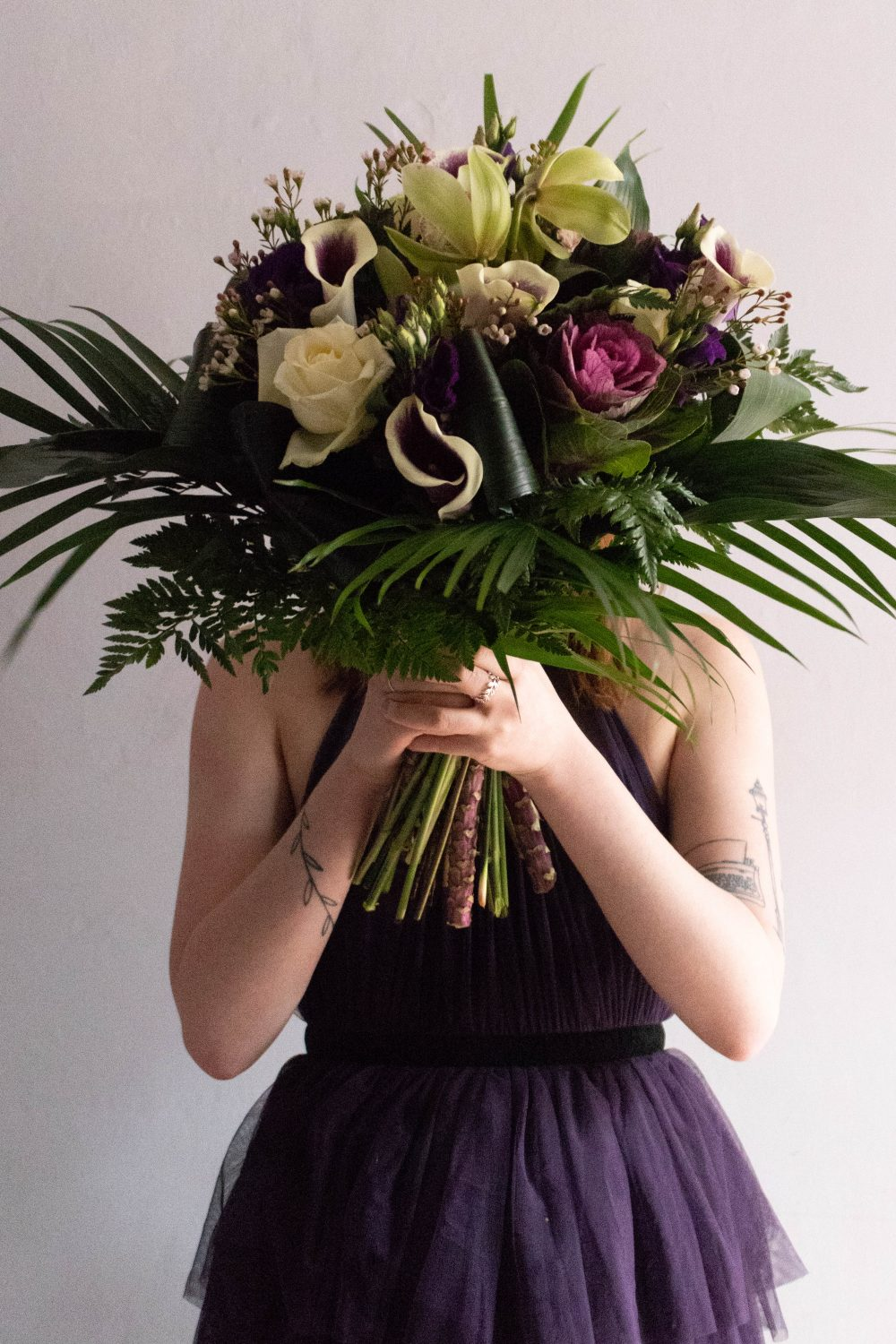 A girl holding a bunch of flowers for a blog post talking about plus one