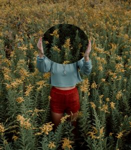 girl with a mirrot in a field in post talkign about identity